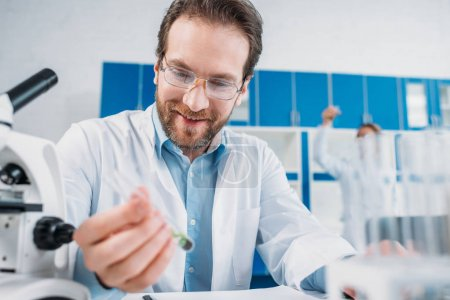 selective focus of smiling scientist in white coat and eyeglasses looking at flask with reagent in hand in laboratory