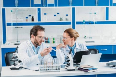 portrait of scientific researchers in white coats at workplace with flasks, microscopes and laptop in laboratory