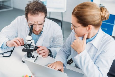 Photo for Portrait of scientific researchers in white coats working together at workplace with microscope  in laboratory - Royalty Free Image