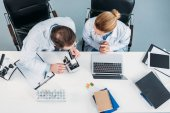 overhead view of scientific researchers in white coats working together at workplace with microscope and laptop in laboratory
