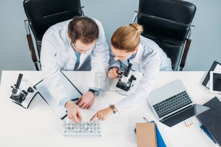 Photo for Overhead view of scientific researchers in white coats looking at flasks with reagents at workplace in laboratory - Royalty Free Image