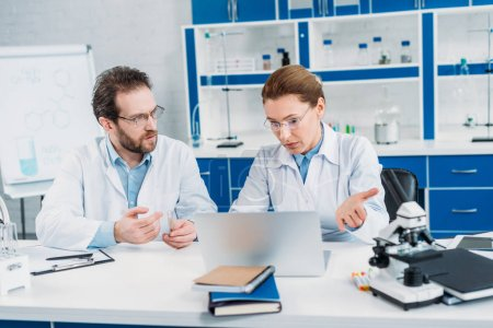 Photo for Portrait of scientists in lab coats and eyeglasses working together at workplace with laptop in lab - Royalty Free Image