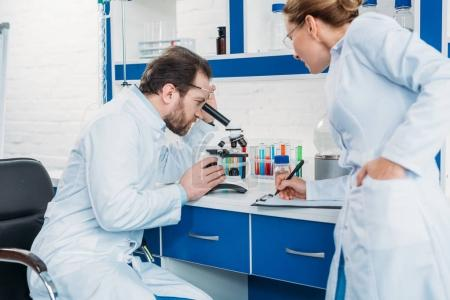 scientific researcher looking through microscope on reagent with colleague near by in laboratory