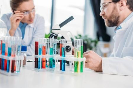 Photo for Selective focus of scientists in eyeglasses at workplace with flasks and microscope in lab - Royalty Free Image