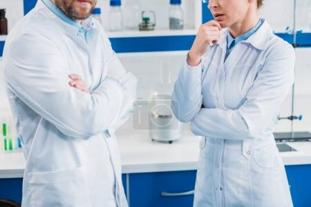 cropped shot on scientists in white coats with arms crossed in lab