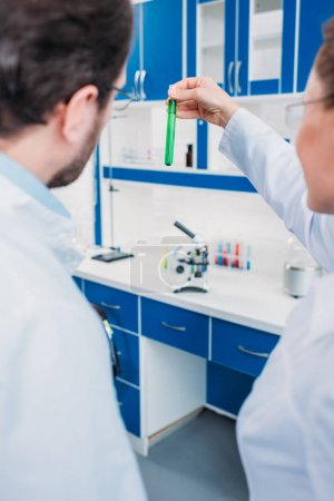 back view of scientists looking at tube with reagent in laboratory