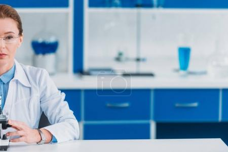 partial view of female scientist in eyeglasses with microscope in laboratory