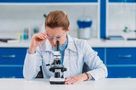 female scientist in eyeglasses looking on reagent through microscope in laboratory