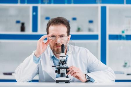 portrait of scientist in white coat and eyeglasses with microscope in laboratory
