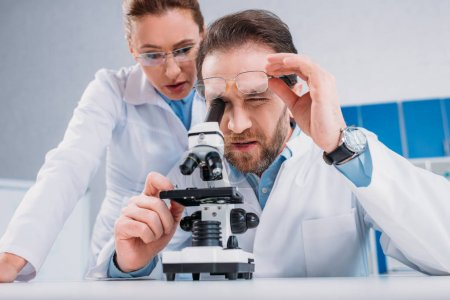 scientists in white coats and eyeglasses working with reagent together in lab