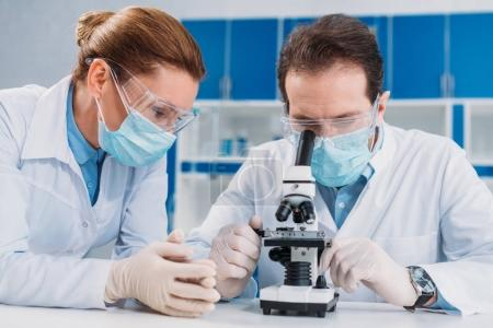 Photo for Portrait of researchers in medical masks and gloves working with microscope together in lab - Royalty Free Image