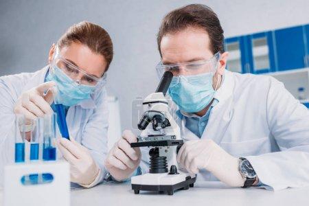 Photo pour Chercheurs en blouses blanches et des masques médicaux travaillent ensemble en laboratoire avec des réactifs en - image libre de droit