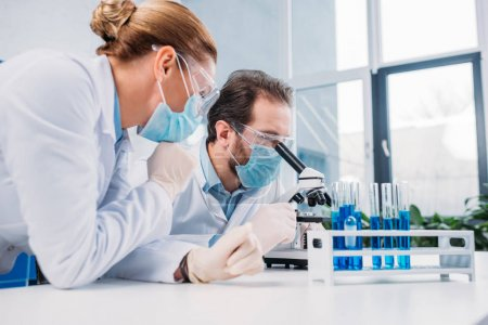 Photo pour Chercheurs en blouse blanche et masques médicaux travaillant ensemble en laboratoire avec des réactifs - image libre de droit