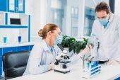scientifiques en blouse blanche et lunettes de travailler avec le microscope en laboratoire et des réactifs