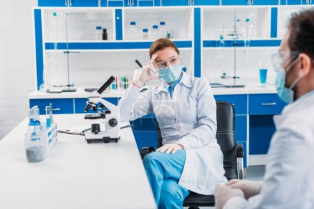 partial view of scientists having discussion at workplace in laboratory