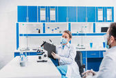 partial view of scientific researchers in white coats at workplace in laboratory