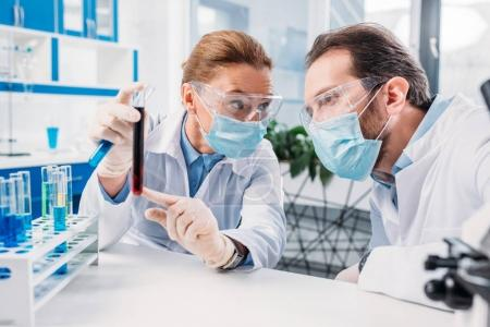 Photo for Scientists in white coats and medical masks working with reagents in laboratory - Royalty Free Image