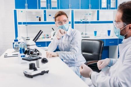 Foto de Investigadores científicos médicos y gafas con debate en lugar de trabajo con microscopio en el laboratorio - Imagen libre de derechos