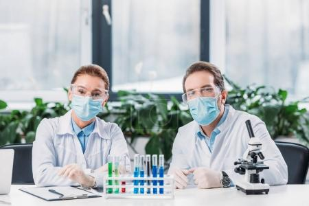 Photo for Scientific researchers in goggles and medical masks sitting at workplace with reagents in tubes and microscope in lab - Royalty Free Image