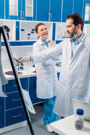 Photo pour Scientifique en blouse blanche près de Conseil pour les notes d'avoir discussion pendant le travail en laboratoire - image libre de droit