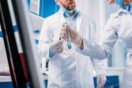 cropped shot of scientists in white coats with tube in lab