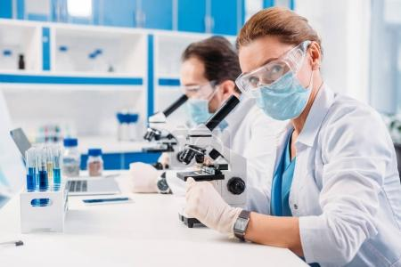 Photo pour Mise au point sélective des scientifiques médicaux masques et lunettes regardant à travers des microscopes sur régents en laboratoire - image libre de droit