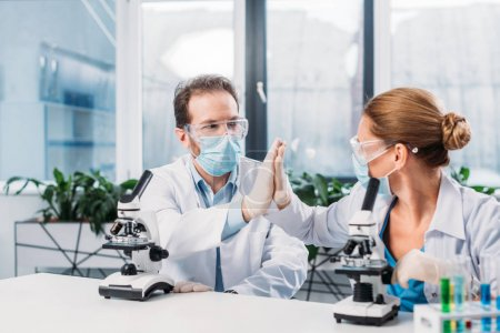 Photo for Scientists in white coats, medical masks and goggles giving high five to each other in lab - Royalty Free Image
