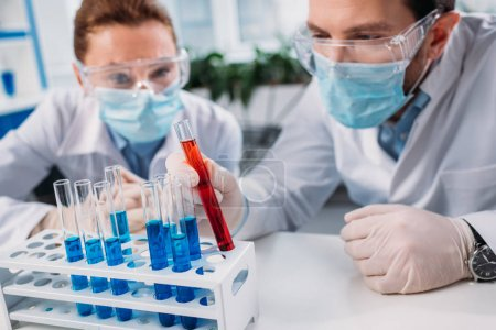 Photo for Selective focus of scientific researchers in goggles and medical masks looking at reagents in tubes in lab - Royalty Free Image