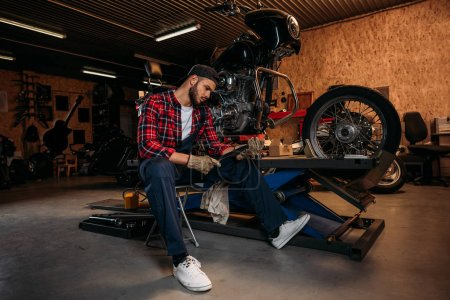 tired bike repair station worker with wrench sitting in front of motorcycle