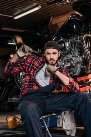 attractive bike repair station worker with wrench sitting in front of motorcycle