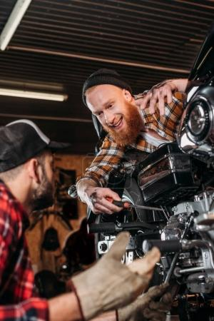 handsome mechanics talking while repairing motorcycle together at garage