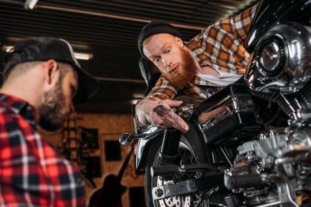 professional mechanics repairing motorcycle together at garage