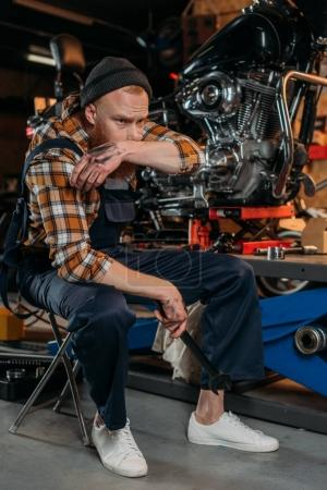 tired bike repair station worker wiping face of sweat after work at garage