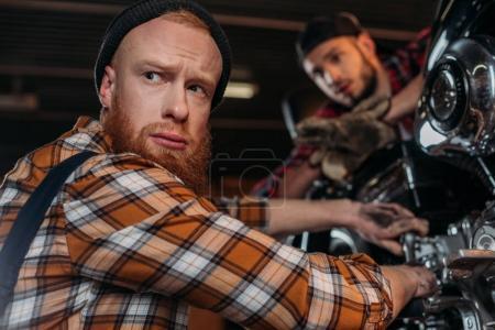 handsome mechanics looking away while repairing motorcycle at garage