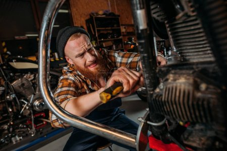 emotional bike repair station worker using screwdriver to fix motorcycle at garage