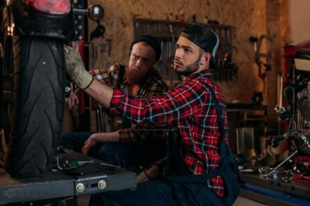 handsome mechanics repairing motorcycle together at garage