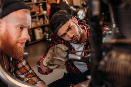 close-up shot of handsome mechanics repairing motorcycle together at garage