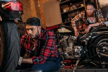 Photo pour Ciblée mécanicien moto tandis que son collègue debout sur fond de fixation - image libre de droit
