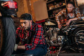 focused mechanic fixing motorcycle while his colleague standing on background