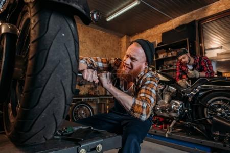 Photo pour Tendu de mécanicien moto tandis que son collègue travaillant sur fond de fixation - image libre de droit