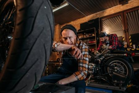 exhausted mechanic wiping sweat after work at garage