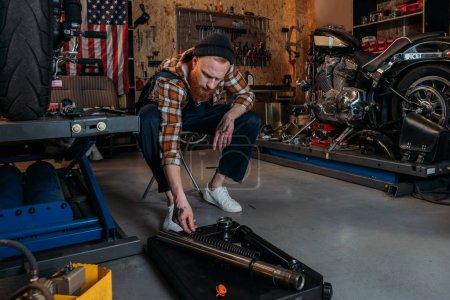 handsome bike repair station worker at garage