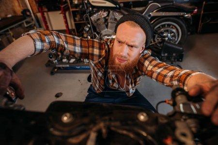 close-up shot of bike repair station worker fixing motorcycle at garage