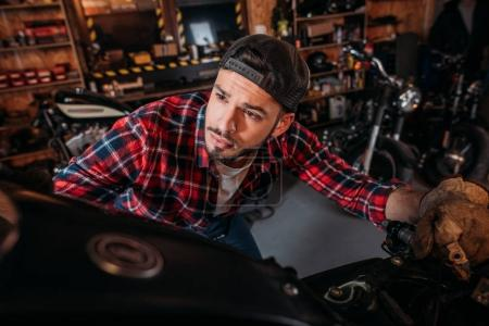 close-up shot of handsome bike repair station worker looking at motorcycle at garage