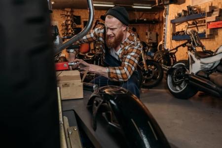 emotional bike repair station worker trying to fix bike at garage