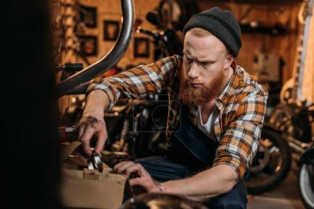 handsome bike repair station worker trying to find details in box at garage