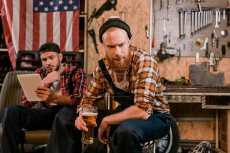 Foto de Apuesto mecánico bebiendo cerveza mientras su colega con tableta en el fondo en el garaje - Imagen libre de derechos