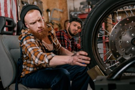 handsome mechanics examining wheel of motorcycle at garage