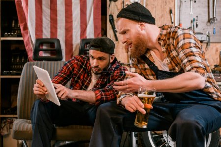 mechanics drinking beer and using tablet together at garage