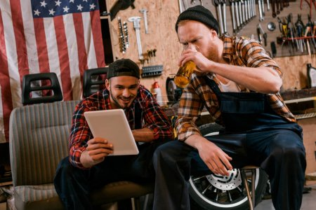young mechanics drinking beer and using tablet together at garage